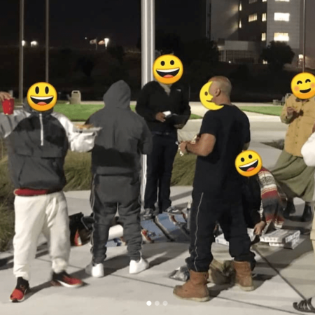 Small group of people with pizza gathered at night in front of Santa Rita Jail