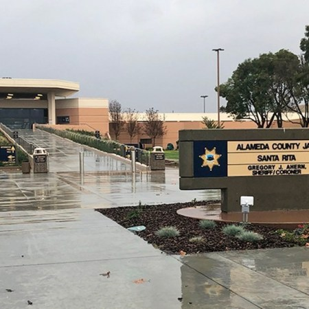 Photo of entrance to Santa Rita Jail on a rainy day. Sign in foreground, long concrete ramp up to imposing concrete structure with entrance. Gray skies above, sidewalks shiny with rain below.